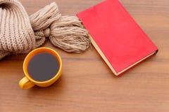Kopp kaffe, stucken halsduk och bok på träbakgrund arkivbild