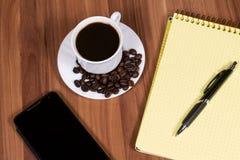 Kopp kaffe, telefon och anteckningsbok Royaltyfri Bild