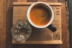 Kopp kaffe varm espresso med exponeringsglas av vatten Fotografering för Bildbyråer