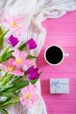 Kopp kaffe, vit gåvaask och anbudbukett av härliga tulpan på rosa träbakgrund Royaltyfri Foto
