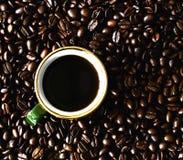 Kopp kaffeanseende på kaffebönor Royaltyfri Fotografi