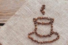 Kopp kaffebönor på bästa sikt för linne Arkivbilder