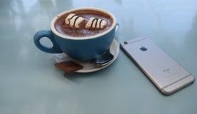 Kopp kaffebakgrundstelefon royaltyfri foto