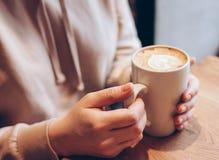 Kopp kaffecappuccino i kvinnliga händer på kafét, slut upp arkivfoto