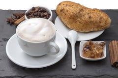 Kopp kaffecappuccino med mjölkar skum på ett tefat, den nya bakade bullen, caramelized socker, kaffebönor, kanel populärt Royaltyfri Foto