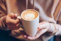 Kopp kaffecappuccino med skumhjärta i kvinnliga händer på kafét, slut upp arkivbilder