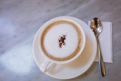 Kopp kaffecapucinokonst på marmortabellen royaltyfri bild
