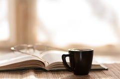 Kopp kaffeexponeringsglas vilar på den öppna boken mot Arkivfoton
