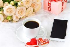 Kopp kaffepepparkakahjärtor, lott av rosor och en telefon på en bakgrund av vit organza valentin för dag s Dagen av wedden Royaltyfri Bild