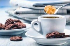 Kopp kaffesked med rottingsocker, chokladkex och bakgrundstidningen Royaltyfria Bilder