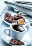Kopp kaffesked med rottingsocker, chokladkex och bakgrundstidningen Arkivfoto