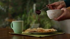 Kopp med ånga och pannkakor på en platta att hälla driftstopp lager videofilmer