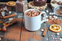 Kopp med beve och marshmallow som strilas med kakaopulver Arkivfoto