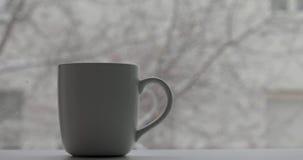 Kopp med en varm drink och snönedgångar arkivfilmer