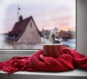 Kopp med en varm drink på fönsterbrädan royaltyfri bild