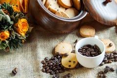 Kopp med kaffebönor och kakor Arkivbilder