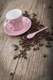 Kopp med kaffebönor på träyttersida Arkivfoto
