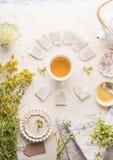 Kopp med ramen av tepåsar av örtte på vit tabellbakgrund, bästa sikt Örtteinställning med tekannan, honung och nytt royaltyfria foton