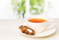 Kopp med te och kex på ett tefat på tabellen arkivbild