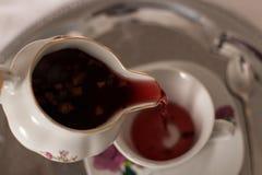 Kopp med te och tekannan, slut upp Arkivfoto