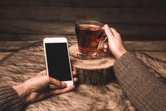 Kopp med te och telefonen i händerna av en flicka på en träbakgrund fotografering för bildbyråer