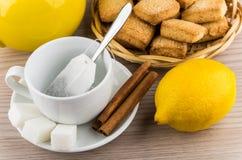Kopp med tepåsen, socker och kanel, citron och kakor Royaltyfri Foto