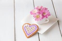 Kopp mycket av rosa mumblommor och hjärtaformkakan på vit w Arkivbilder