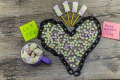 Kopp- och kedjeform av hjärta med ordet 14th februari och marshmallower Arkivbilder