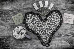 Kopp- och kedjeform av hjärta med ordet 14th februari och marshmallower Arkivbild