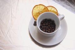 Kopp och tefat, kaffebönor, skivor av den torkade apelsinen på en silvertabell royaltyfri foto