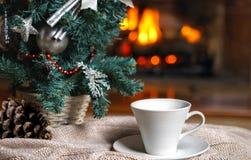 Kopp te eller kaffe, woolen stucken sakerpläd och julpynt nära hemtrevlig spisbakgrund, i landshus cozy royaltyfri bild