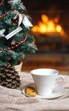 Kopp te eller kaffe, woolen stucken sakerpläd och julpynt nära hemtrevlig spisbakgrund, i landshus cozy arkivfoto