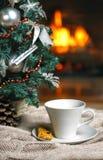 Kopp te eller kaffe, woolen stucken sakerpläd och julpynt nära hemtrevlig spisbakgrund, i landshus cozy arkivbilder