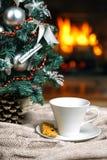 Kopp te eller kaffe, woolen stucken sakerpläd och julpynt nära hemtrevlig spisbakgrund, i landshus cozy royaltyfria bilder