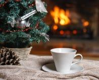 Kopp te eller kaffe, woolen stucken sakerpläd och julpynt nära hemtrevlig spisbakgrund, i landshus cozy arkivfoton