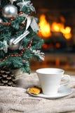 Kopp te eller kaffe, woolen stucken sakerpläd och julpynt nära hemtrevlig spisbakgrund, i landshus cozy royaltyfri fotografi