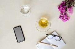 Kopp te för bästa sikt med blomman, mobiltelefon, exponeringsglas av vatten och Royaltyfri Bild