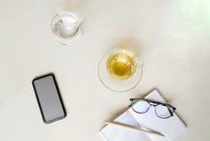 Kopp te för bästa sikt med mobiltelefonen, exponeringsglas av vatten och exponeringsglas Arkivbild