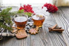 Kopp te, granfilial, röda bär, ljust rödbrun kakor och kanel på trätabellen royaltyfri fotografi