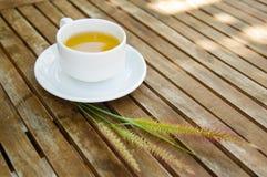 Kopp te & gruppen av Cenchrussetaceusgräs blommar på trä Royaltyfri Bild