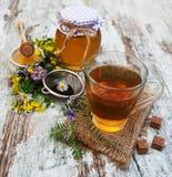 Kopp te, honung och blommor Fotografering för Bildbyråer