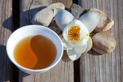 Kopp te i form av det Yin Yang symbolet med en näckros överkant arkivbild