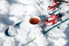 Kopp te i snön och att skida royaltyfri foto