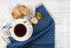 Kopp te, kakor och klocka på en trävit texturerad tabell, Arkivbild