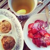 Kopp te med bakelse och jordgubbar Arkivfoton