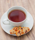 Kopp te med biscotti Arkivfoton
