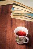 Kopp te med bunten av gamla böcker arkivbilder
