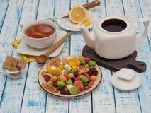 Kopp te med citronen, en tekanna och torkade frukter på en trätabell arkivbilder