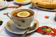 Kopp te med citronen på tabellen Arkivbild