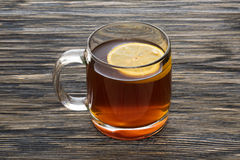Kopp te med citronen på trätabellen Arkivfoto